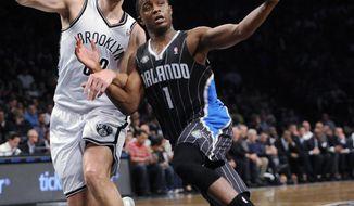 Brooklyn Nets' Mirza Teletovic (33) defends Orlando Magic's Doron Lamb (1) duirng the second half of an NBA basketball game Sunday, April 13, 2014, in New York. The Nets won 97-88. (AP Photo/Kathy Kmonicek)