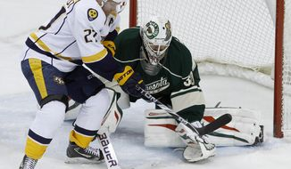 Minnesota Wild goalie Ilya Bryzgalov, right, of Russia, swats away a shot past Nashville Predators right wing Patric Hornqvist, left, of Sweden, during the first period of an NHL hockey game in St. Paul, Minn., Sunday, April 13, 2014. (AP Photo/Ann Heisenfelt)