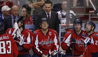 Washington Capitals head coach Adam Oates, top center, stands behind right wing Alex Ovechkin (8), from Russia, in the overtime portion of an NHL hockey game against the Tampa Bay Lightning, Sunday, April 13, 2014, in Washington. The Lightning won 1-0 in a shootout. (AP Photo/Alex Brandon)