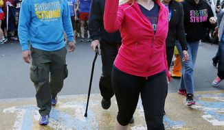 Boston Marathon bombing survivor Heather Abbott carries a symbolic torch as she crosses the marathon finish line in Boston, Sunday, April 13, 2014,  for the last leg of a cross country charity run that began in March in California. Abbott, along with other survivors and family members joined the relay runners for the final half-block to the finish. (AP Photo/Michael Dwyer)