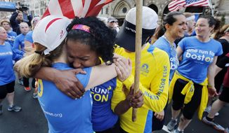 Rosa Evora, center, hugs a fellow participant in a cross country relay that began in March in California and ended at the Boston Marathon finish line in Boston, Sunday, April 13, 2014.  Boston Marathon bombing survivors, family members and supporters joined the relay runners for the final half-block to the finish. (AP Photo/Michael Dwyer)