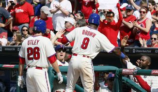 Philadelphia Phillies' Chase Utley, left, and Domonic Brown return to high-fives in the dugout after scoring on a double by Wil Nieves during the fifth inning of a baseball game against the Miami Marlins, Sunday, April 13, 2014, in Philadelphia. (AP Photo/Tom Mihalek)