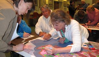 In this March 18, 2014 photo, Darlene Greene, left, reviews maps of Toms River N.J. that show flooding damage from Superstorm Sandy with Jeff Coley, center, and Jo-Ann Herbst. They were at a hearing at the Toms River municipal building for residents to make suggestions on how to protect against future storms. Ideas included building dunes, adding bulkheading, better securing boats and floating docks, and monitoring the slope of homeowners' properties to avoid channeling water into low-lying areas. (AP Photo/Wayne Parry)