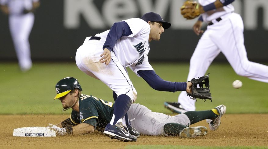 Oakland Athletics' Eric Sogard, left, is safe stealing second as Seattle Mariners shortstop Brad Miller waits for the throw in the sixth inning of a baseball game on Saturday, April 12, 2014, in Seattle. (AP Photo/Ted S. Warren)