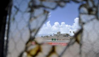 FILE - In this Aug. 23, 2013 pool file photo reviewed by the U.S. Department of Defense, one of Guantanamo Bay's two courthouses is seen through a broken window at Camp Justice at the Guantanamo Bay U.S. Naval Base, Cuba. On Monday, April 14, 2014 a judge in Guantanamo will open a hearing into the sanity of prisoner Ramzi Binalshibh, whose courtroom outbursts about alleged mistreatment in Camp 7 have halted the effort to try five men in the Sept. 11 attacks, all of whom are held there. (AP Photo/Toronto Star, Michelle Shephard, Pool, File)