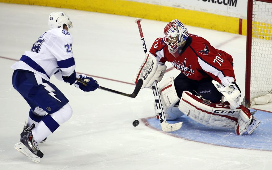 Tampa Bay Lightning defenseman Matt Carle (25) shoots the game-winning goal past Washington Capitals goalie Braden Holtby (70) in the shootout portion of an NHL hockey game on Sunday, April 13, 2014, in Washington. The Lightning won 1-0. (AP Photo/Alex Brandon)