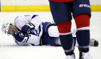 Tampa Bay Lightning center Tyler Johnson (9) lies on the ice with an injury in the second period of an NHL hockey game against the Washington Capitals, Sunday, April 13, 2014, in Washington. (AP Photo/Alex Brandon)