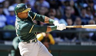 Oakland Athletics' Yoenis Cespedes hits a two-run home run against the Seattle Mariners in the eighth inning of a baseball game Sunday, April 13, 2014, in Seattle. (AP Photo/Elaine Thompson)