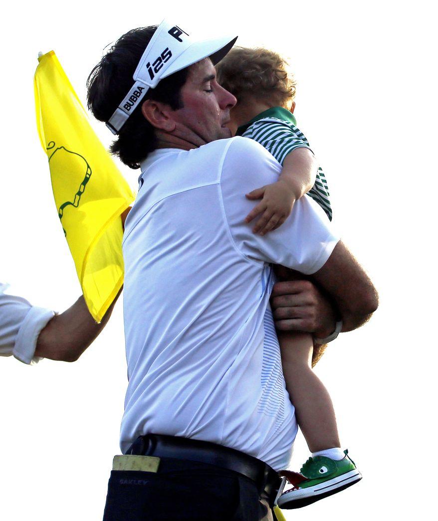 Bubba Watson carries his son Caleb after winning the Masters golf tournament Sunday, April 13, 2014, in Augusta, Ga. (AP Photo/Matt Slocum)
