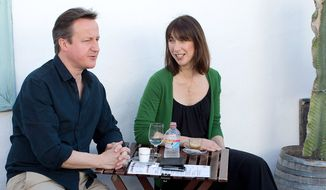 British Prime Minister David Cameron, left, and his wife Samantha stop for a drink by a beach during their holiday on the Spanish Island of Lanzarote, Sunday, April 13, 2014.  (AP Photo/Gonzalo Arroyo Moreno, pool)