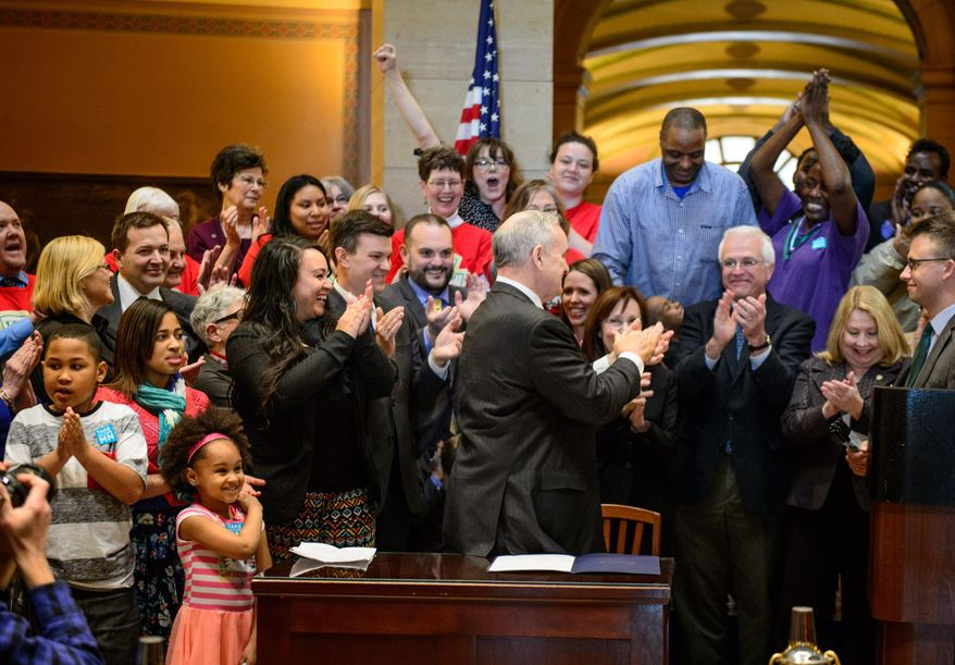 The crowd cheers after Governor Mark Dayton signed the minimum wage bill into law at a public bill signing ceremony Monday, April 14, 2014 at the Minnesota State Capitol Rotunda in St. Paul.  Minnesota goes from having one of the nation's lowest minimums to among the highest. With federal wage legislation stuck in Congress, states are rushing to fill the void.   (AP Photo/The Star Tribune, Glen Stubbe)  MANDATORY CREDIT; ST. PAUL PIONEER PRESS OUT; MAGS OUT; TWIN CITIES TV OUT