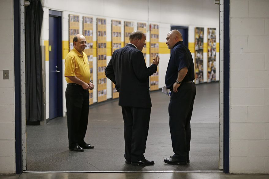 Nashville Predators head coach Barry Trotz, right, talks with Predators CEO Jeff Cogen, center, after Trotz appeared at a news conference Monday, April 14, 2014, in Nashville, Tenn. The Predators announced earlier in the day that Trotz's contract won't be extended and they will begin looking for a new head coach. Trotz is the only head coach the NHL hockey team has had. At left is Gerry Helper, Predators senior vice president of hockey communications and public relations. (AP Photo/Mark Humphrey)