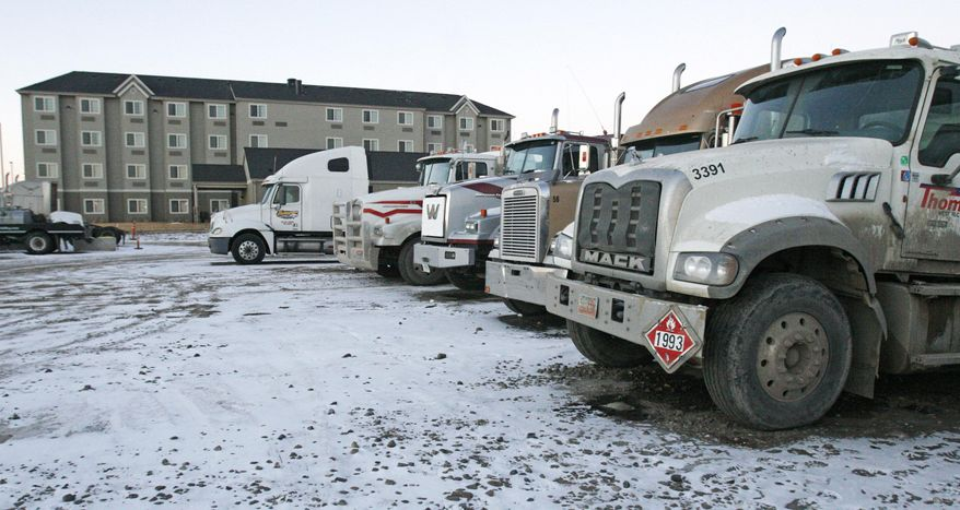 Trucks sit in a parking lot outside one of many newer multi-story hotels in Williston, N.D. on Tuesday, Feb. 25, 2014. Williston is the hub for the Bakken shale fields oil boom in North Dakota. Because of a housing shortage, the hotels often serve as temporary housing for oil workers. Big money is raining down in small towns. But the bonanza suddenly flourishing here has also brought with it a dark side: a growing trade in meth, heroin, cocaine and marijuana, drug cartels and newfound violence. (AP Photo/Martha Irvine)