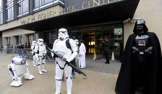 Star Wars characters stand in front of the Max M. Fisher Music Center in Detroit on Monday, April 14, 2014 in Detroit. Tickets for a special concert in Detroit featuring director Steven Spielberg and composer John Williams sold out in record time. The Detroit Symphony Orchestra says tickets to the show were snapped up 15 minutes after they went on sale to the general public at 9 a.m. Monday. That's a Detroit Symphony box-office record. Fans camped out overnight for the June 14 concert that will benefit the DSO.  (AP Photo/Detroit News, David Coates)  DETROIT FREE PRESS OUT; HUFFINGTON POST OUT
