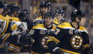 Boston Bruins' David Krejci (46) celebrates his goal with teammates during the first period of an NHL hockey game against the Buffalo Sabres in Boston, Saturday, April 12, 2014. The Bruins won 4-1. (AP Photo/Michael Dwyer)
