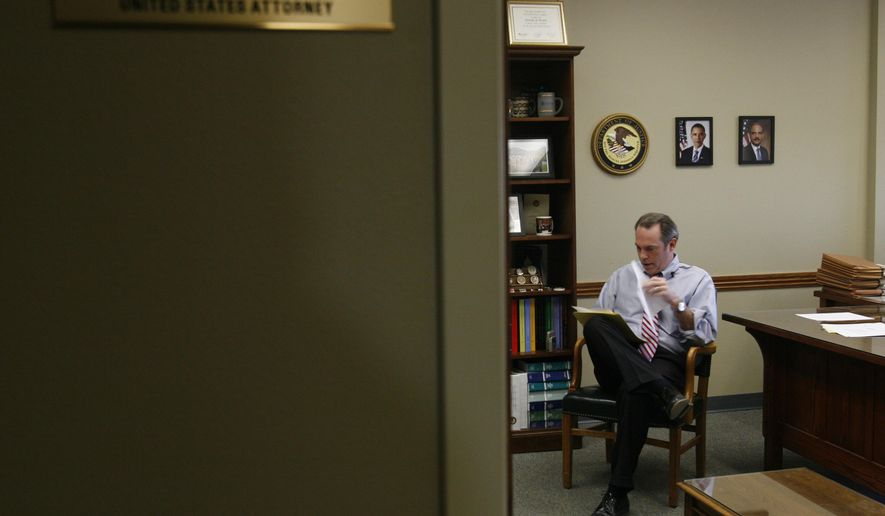"Timothy Purdon, the U.S. attorney for North Dakota, looks through documents related to drug cases in his office in Bismarck, N.D. on Monday, Feb. 24, 2014. ""Organized drug dealers are smart,"" he says. ""They're good businessmen. They go where the demand is and that's what they're seeing there. ... There's simply a lot of money flowing in these communities."" (AP Photo/Martha Irvine)"