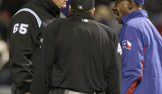 Texas Rangers manager Ron Washington, right, argues a call with umpires Ted Barrett (65) and Paul Schrieber during the sixth inning of a baseball game against the Seattle Mariners Monday, April 14, 2014, in Arlington, Texas. Washington was ejected from the game after the call was made. (AP Photo/LM Otero)