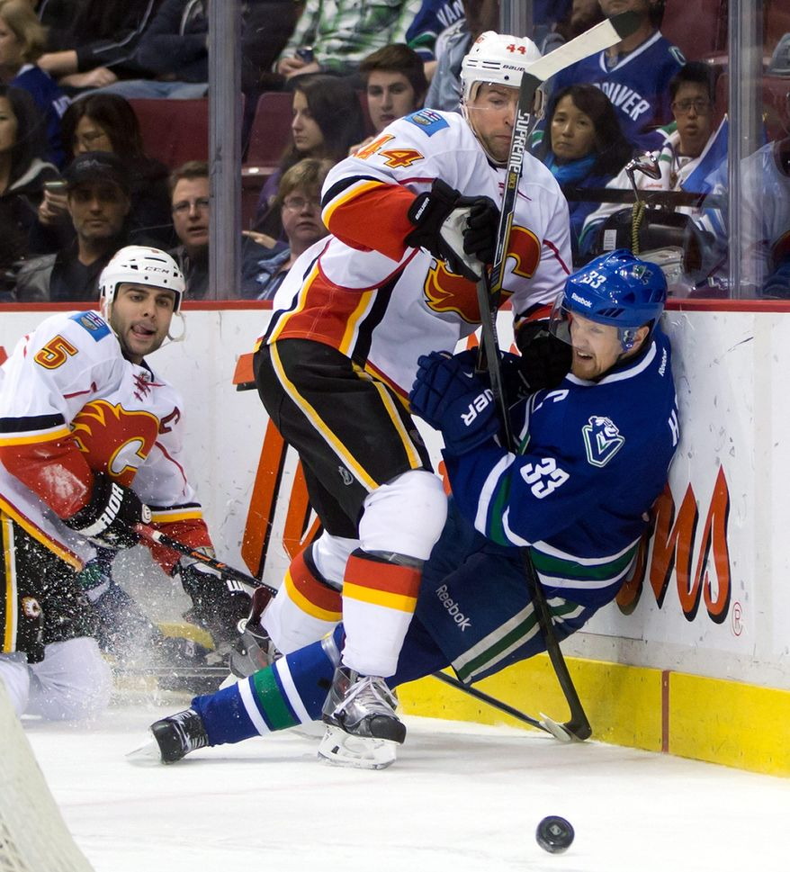 Calgary Flames' Chris Butler, centre, checks Vancouver Canucks' Henrik Sedin, of Sweden, as Flames' Mark Giordano, left, watches during second period NHL hockey action in Vancouver, British Columbia, on Sunday April 13, 2014. (AP Photo/The Canadian Press, Darryl Dyck)