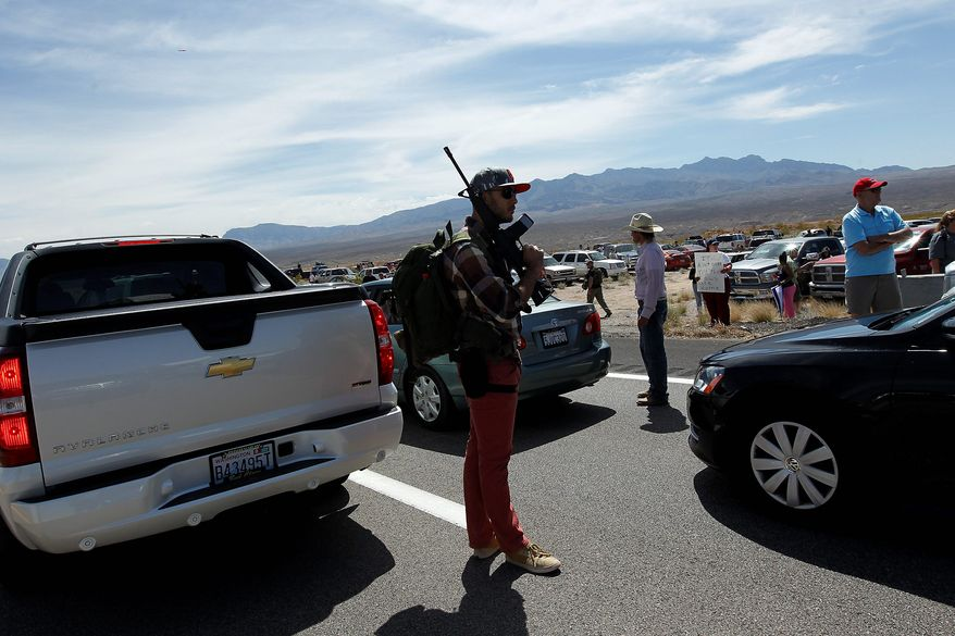 Tyler Lewis, from St. George, Utah, stands in the middle of northbound Interstate 15 with his gun near Bunkerville, Nev., while gathering with other supporters of the Bundy family to challenge the Bureau of Land Management on Saturday. (Associated Press)