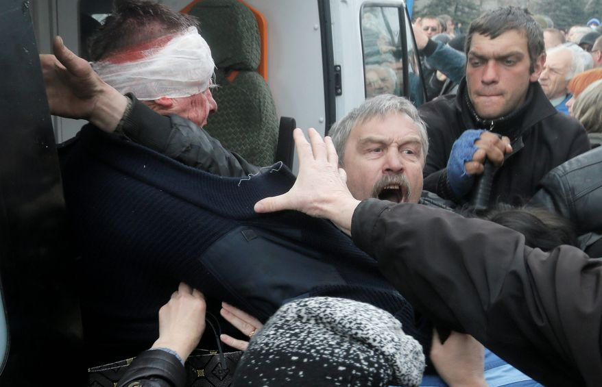 A man tries to protect a Ukrainian police officer beaten by a pro-Russian mob that stormed a police station in Horlivka, eastern Ukraine, Monday. A pro-Russian mob seized a police building in yet another city in Russian-leaning eastern Ukraine, defying government warnings that it was preparing to act against the insurgents. (Associated Press)