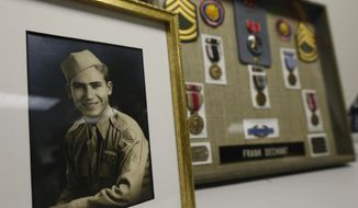 A framed photo and medals, including a Bronze Star, sit on display during a ceremony at which 91-year-old World War II veteran Frank Dechant  received the United States Prisoner of War Medal, in Lakewood, Colo., Monday April 14, 2014. Dechant was captured in Belgium in 1944 during the infamous Battle of the Bulge, in which there were more than 80,000 American casualties. Liberation for Dechant came in April 1945 after a two-month, forced march ahead of the Soviet advance into Germany. (AP Photo/Brennan Linsley)