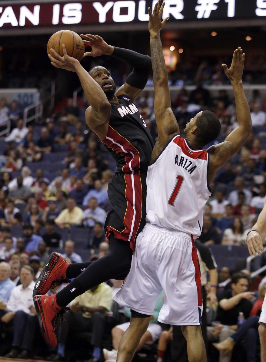Miami Heat guard Dwyane Wade (3) shoots over Washington Wizards forward Trevor Ariza (1) in the first half of an NBA basketball game, Monday, April 14, 2014, in Washington. (AP Photo/Alex Brandon)