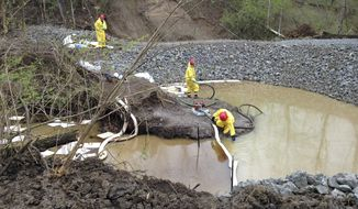 Crews check absorbent booms and pads at the site of a dam and containment basin at Oak Glen Nature Preserve near Cincinnati, Monday, April 14, 2014. Federal officials have estimated that more than 20,000 gallons of crude leaked from a 5-inch crack in an oil pipeline four weeks ago. (AP Photo/Lisa Cornwell)