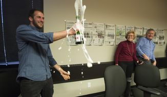 "Colorado Springs Gazette photographer Michael Ciaglo pops the cork on a bottle of champagne after the announcement Monday, April 14, 2014, that Gazette reporter David Philipps won a Pulitzer Prize for The Gazette's ""Other Than Honorable"" series. Ciaglo was the photographer on the project that won the  National Reporting award. (AP Photo/The Colorado Springs Gazette, Mark Reis) MAGS OUT"