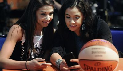 Future draftee Louisville's Shoni Schimmel, right, and her sister, Louisville player Jude Schimmel look at Schimmel's phone proir to the start of the WNBA basketball draft in, Monday, April 14, 2014, in Uncasville, Conn. (AP Photo/Jessica Hill)