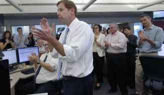 In this photo released by The Boston Globe, editor Brian McGrory and members of the newsroom applaud after The Globe was awarded the Pulitzer Prize for breaking news for coverage of the 2013 Boston Marathon bombings, Monday, April 14, 2014, in Boston. Monday's announcement came as the city prepares for Tuesday's anniversary of the bombing. (AP Photo/The Boston Globe, Jessica Rinaldi)