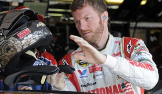 Dale Earnhardt Jr. reaches for his helmet before a NASCAR Sprint Cup series auto race practice at Darlington Speedway in Darlington, S.C., Friday, April 11, 2014. (AP Photo/Mike McCarn)