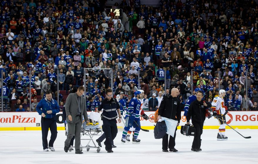 Vancouver Canucks' Daniel Sedin, of Sweden, is taken off the ice on a stretcher after being checked into the boards by Calgary Flames' Paul Byron during second period NHL hockey action in Vancouver, British Columbia, on Sunday April 13, 2014. (AP Photo/The Canadian Press, Darryl Dyck)