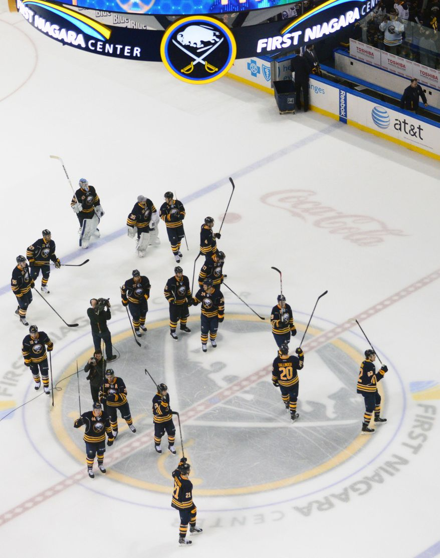 Buffalo Sabres gather at center ice to salute fans following their final regular season NHL hockey game against the New York Islanders' in Buffalo, N.Y., Sunday, April 13, 2014. (AP Photo/Adam Wiepert)
