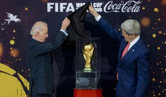 Vice President Joseph R. Biden (left) and Secretary of State John Kerry unveil the FIFA World Cup trophy, the actual trophy that will be awarded to the winner of this year's World Cup soccer tournament in Brazil, during a ceremony at the State Department in Washington on April 14, 2014. (Associated Press)