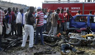People gather at the site of a blast at the Nyanya Motor Park, about 16 kilometers (10 miles) from the center of Abuja, Nigeria, Monday, April 14, 2014. An explosion blasted through a busy commuter bus station on the outskirts of Abuja before 7 a.m. (0600 GMT) Monday as hundreds of people were traveling to work. (AP Photo/Gbemiga Olamikan)
