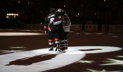 Anaheim Ducks' Teemu Selanne, left, of Finland, and Colorado Avalanche goalie Jean-Sebastien Giguere, who plan to retire after the season, hug as they are honored after an NHL hockey game on Sunday, April 13, 2014, in Anaheim, Calif. The Ducks won 3-2 in overtime. (AP Photo/Jae C. Hong)