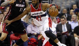 Washington Wizards forward Nene (42), from Brazil, drives against Miami Heat forward Chris Andersen (11) in the first half of an NBA basketball game, Monday, April 14, 2014, in Washington. (AP Photo/Alex Brandon)