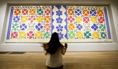 A woman adjusts her hair as she poses for photographers in front of 'Large Composition with Masks 1953' by Henri Matisse, on display during a media opportunity at The Tate Modern in London, Monday, April 14, 2014. The artwork is part of the 'Henri Matisse: The Cut-Outs' exhibition that runs at the gallery from April 17 until Sept. 7, 2014. (AP Photo/Kirsty Wigglesworth)