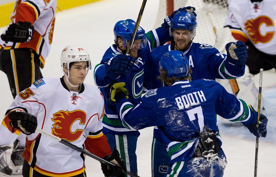 Calgary Flames' Sean Monahan, from left to right, skates to the bench as Vancouver Canucks' Henrik Sedin, of Sweden, Daniel Sedin, of Sweden, and David Booth celebrate Daniel's goal during first period NHL hockey action in Vancouver, British Columbia, on Sunday April 13, 2014. (AP Photo/The Canadian Press, Darryl Dyck)