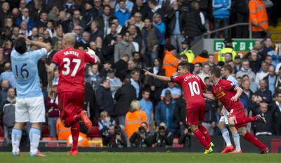 Liverpool's Philippe Coutinho, second right, celebrates after scoring the winning goal against Manchester City during their English Premier League soccer match at Anfield Stadium, Liverpool, England, Sunday April 13, 2014. (AP Photo/Jon Super)