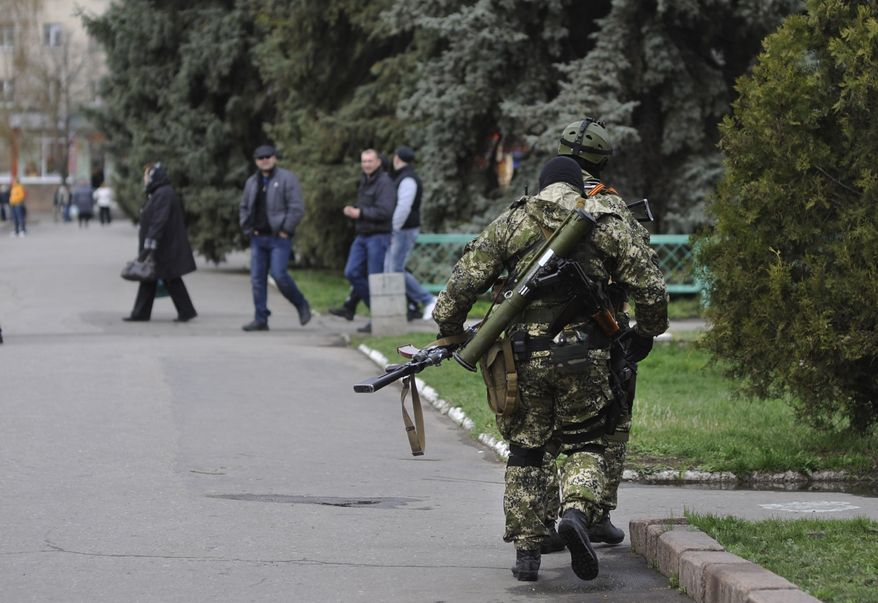 Armed pro-Russian activists walk through a street near to the seized Ukrainian regional administration building in the eastern Ukrainian town of Slovyansk,  Ukraine, Monday, April 14, 2014.  Ukraine's acting president urged the United Nations on Monday to send peacekeeping troops to eastern Ukraine, where pro-Russian gunmen kept up their rampage of storming and occupying local government offices, police stations and a small airport. (AP Photo/Evgeniy Maloletka)