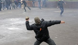 Pro-Russian men throw stones during the mass storming of a police station in Horlivka, eastern Ukraine, Monday, April 14, 2014. Ukraine's acting President Oleksandr Turchynov on Monday called for the deployment of United Nations peacekeeping troops in the east of the country, where pro-Russian insurgents have occupied buildings in nearly 10 cities. (AP Photo/Efrem Lukatsky)