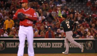 Oakland Athletics' John Jaso, right, rounds third after hitting two-run home run as Los Angeles Angels relief pitcher Ernesto Frieri looks on during the ninth inning of a baseball game, Monday, April 14, 2014, in Anaheim.  (AP Photo/Mark J. Terrill)