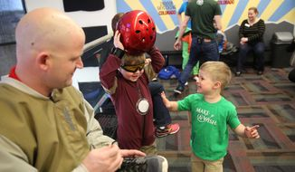 CORRECTS TO CHARLIE, NOT ROWEN - Charlie Vertin, 3, watches as his brother, Max, 7, puts on a helmet for his Iron Man costume before going into a wind tunnel simulating free fall during a day hosted by the Make-A-Wish Foundation at SkyVenture Colorado in Lone Tree, Colo., south of Denver, on Tuesday April 15, 2014. Vertin and his two brothers have Duchenne muscular dystrophy, a rare disease which will cause their muscles to slowly deteriorate. Their father, Jason, is at right. (AP Photo/Brennan Linsley)