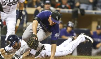 San Diego Padres' Xavier Nady slides in safely as Colorado Rockies relief pitcher Rex Brothers can't catch the throw from the catcher after a wild pitch in the eighth inning of a baseball game Monday, April 14, 2014, in San Diego. Two runs scored on the play and Padres won the game 5-4. (AP Photo/Lenny Ignelzi)