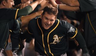 Oakland Athletics' John Jaso runs through a gauntlet of teammates after hitting two-run home during the ninth inning of a baseball game against the Los Angeles Angels, Monday, April 14, 2014, in Anaheim.  (AP Photo/Mark J. Terrill)