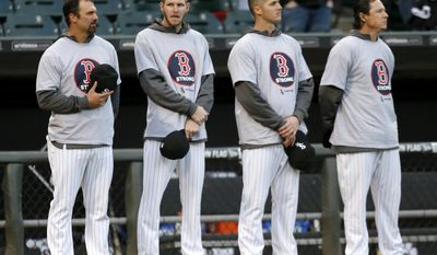 Members of the Chicago White Sox, from left, Paul Konerko, Chris Sale, Nate Jones, and Scott Downs stand wearing Boston Strong shirts before the White Sox's baseball game against the Boston Red Sox on Tuesday, April 15, 2014, in Chicago. (AP Photo/Charles Rex Arbogast)