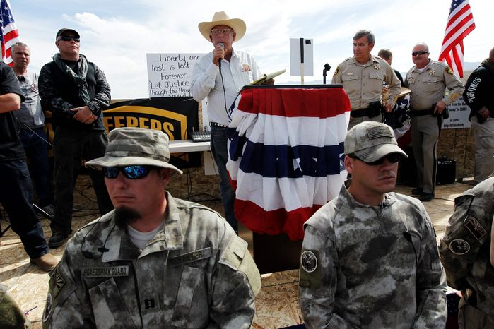 """Rancher Cliven Bundy (center) addresses his supporters as Clark County Sheriff Doug Gillespie (right) looks on Saturday. Ryan Yates, director of congressional relations for the American Farm Bureau, decried what he says some have called """"a culture of intimidation"""" represented in the standoff over grazing rights between the rancher and the federal Bureau of Land Management. (ASSOCIATED PRESS)"""
