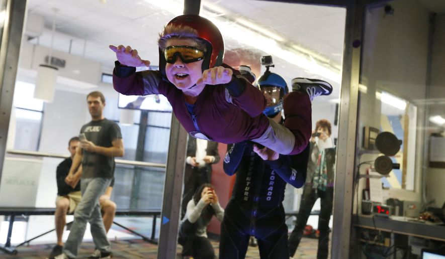 Wearing an Iron Man costume, Max Vertin, 7, from Hastings, Neb., floats in a wind tunnel simulating free fall during a day hosted by the Make-A-Wish Foundation at SkyVenture Colorado in Lone Tree, Colo., south of Denver, on Tuesday April 15, 2014. Vertin and his two brothers have Duchenne muscular dystrophy, a rare disease which causes their muscles to slowly deteriorate. Despite his medical condition, his parents say he is a regular kid who likes the color orange, pizza, collecting bugs, and his favorite superhero, Iron Man. (AP Photo/Brennan Linsley)