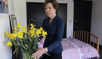 File - In this Jan. 25, 2014 file photo, Lorraine Rorke Bader arranges fresh flowers in a room at her home before an overnight guest arrives in San Francisco. Bader rents out the room, with a 3-night minimum stay, for $120 a day using the Airbnb service. Legislation set to be unveiled Tuesday, April 15, 2014, by a San Francisco supervisor would make it legal for city residents to rent out their homes on sites such as Airbnb, but only if they have liability insurance and meet other requirements. (AP Photo/San Francisco Chronicle, Paul Chinn, File)